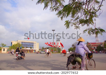 HUE, VIETNAM - APRIL 14 : The women Vietnamese is driving by her bicycle to go to local market in Hue, Vietnam on April 14, 2011. - stock photo