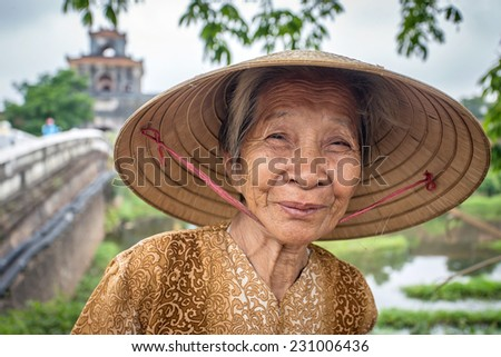 HUE, VIETNAM - APRIL 3, 2014: Unidentified Vietnamese woman wearing traditional conical hat poses for the camera in Hue, Vietnam on April 3, 2014. - stock photo