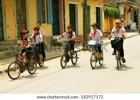 HUE, VIETNAM - MARCH 10, 2013: Unidentified schoolboys biking to home after studying in Hue, Vietnam at March 10, 2013.