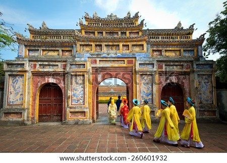 HUE, VIETNAM - May 1, 2014 : People in traditional costumes walk under an archway in the Imperial City of Hue, Vietnam. - stock photo