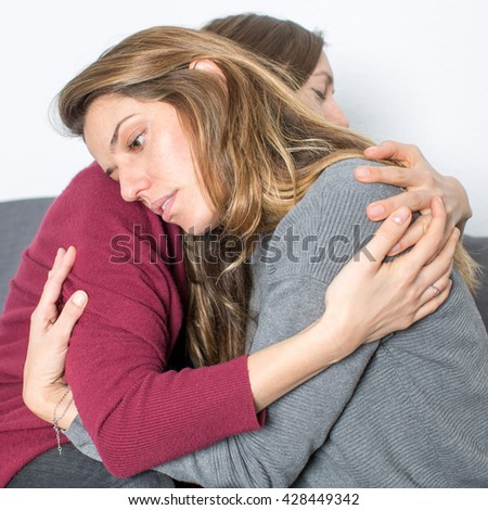Hug between girlfriends sitting on a sofa - stock photo