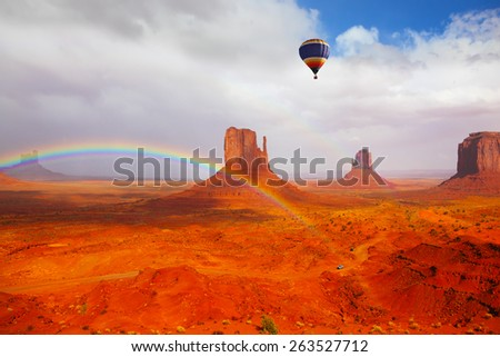 "Huge balloon flies over Red Desert Navajo, USA. The picturesque rainbow crosses some rocks - ""mitts"" - stock photo"