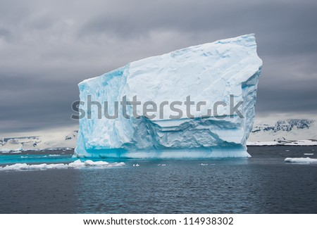 Huge blue iceberg in the antarctic waters - stock photo