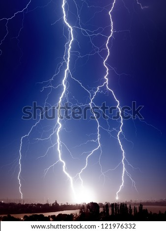 Huge bolt of lightnings hits small town - stock photo