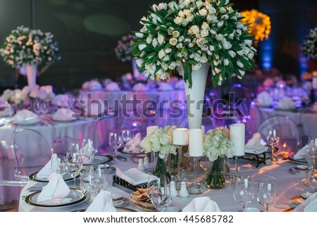 Huge bouquet of white tulips stand in high thin vase on a dinner table