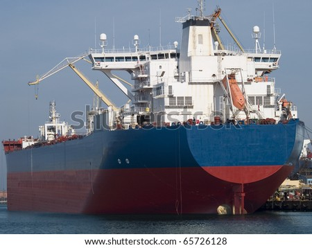 Huge cargo ship moored to a wharf - stock photo