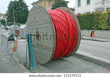 huge coils of red high-voltage power cable in the middle of the road - stock photo