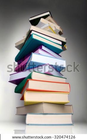 Huge column of books isolated on retro style background. - stock photo