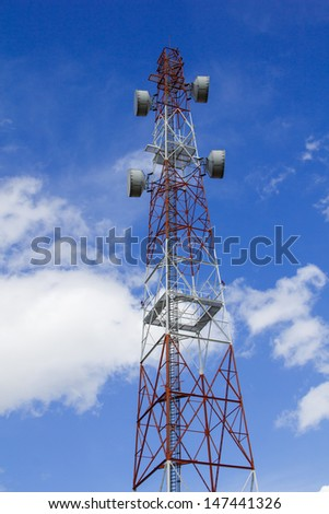 Huge communication antenna tower and satellite dishes against blue sky