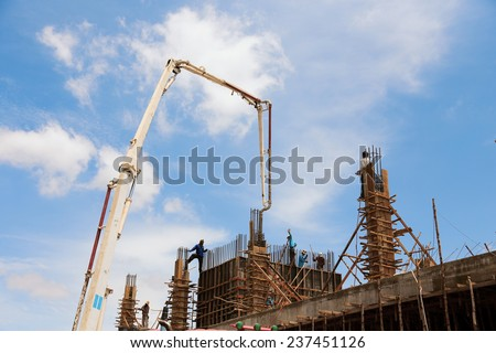 Huge concrete pump with tall arm pumping concrete on top of the building with workes  - stock photo