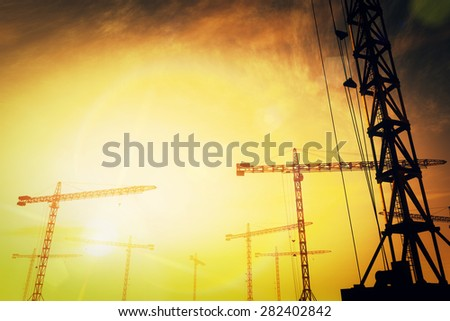Huge Construction Cranes in Industrial Zone in Sunset Sunrise 3D ArtworkConcept of construction, heavy industry, commerce and architecture. - stock photo