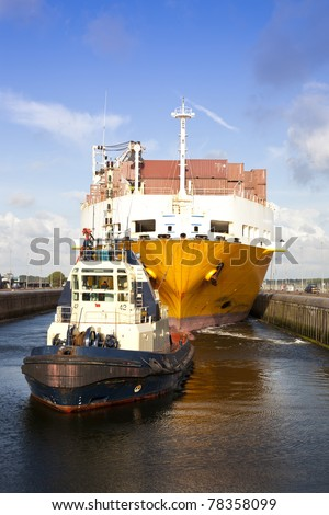 Huge container ship with tug boat in lock - stock photo