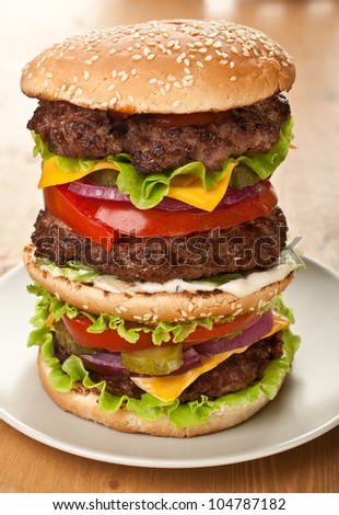 huge double tasty cheeseburger on a plate - stock photo