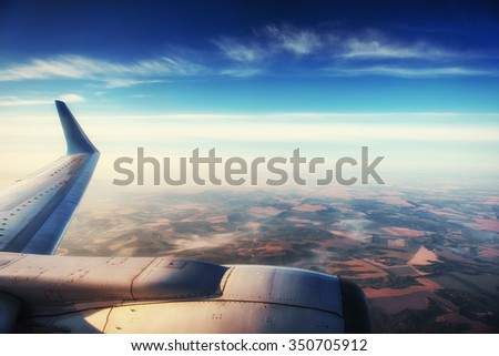 huge fields and small town seen through the window of jet airplane in bright sunny day - stock photo
