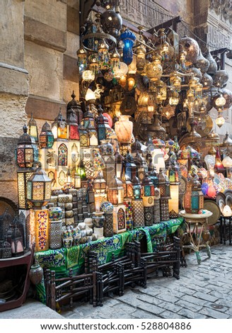 Huge group of stacked illuminated copper lanterns over background of old stone wall and basalt tiles floor at Khan El Khalili bazaar district, one of Old Cairo's main attractions for tourists