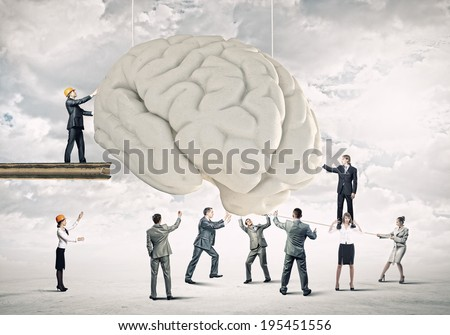 Huge human brain and many little businesspeople around - stock photo