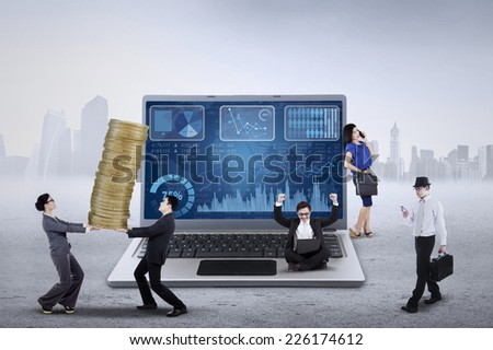 Huge laptop with financial chart on the screen and busy businesspeople - stock photo