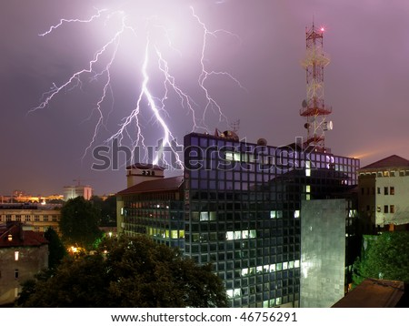 huge lightning bolt behind glass office building with communication tower