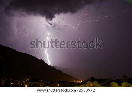 Huge Lightning bolt over hill - stock photo