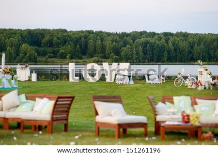 Huge LOVE letters as a fancy wedding decoration on a river bank - stock photo