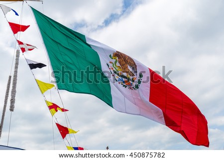 Huge Mexican flag weaving against sky background - stock photo