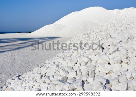 Huge piles of white marble pebbles in different granulation beside blue sea on Thassos in Greece - stock photo