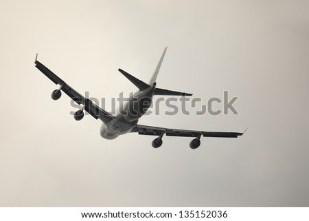 Huge plane taking off to overcast sky - stock photo