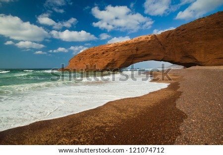 Huge red cliff with arch on the beach Legzira. Morocco - stock photo