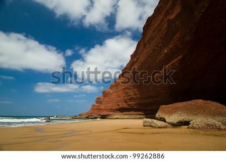 huge red cliffs on the beach Legzira. Morocco - stock photo