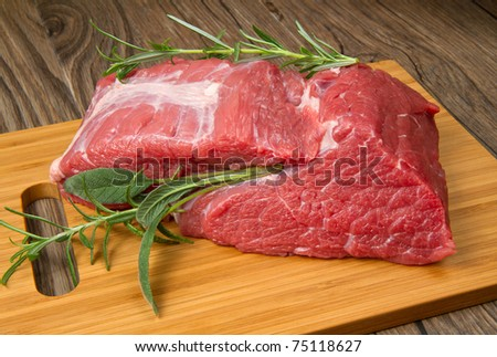 huge red meat chunk on wooden table - stock photo