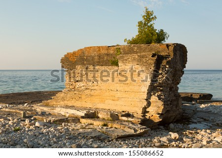 Huge rock with juniper tree on top of it on a shore of Lake Huron, Bruce Peninsula, Ontario, Canada - stock photo