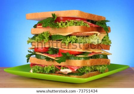 Huge sandwich on blue background - stock photo