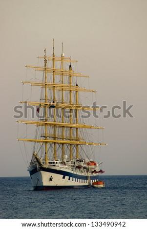 Huge ship with sail navigating seashore of Sicily/Ship sailing at twilight - stock photo