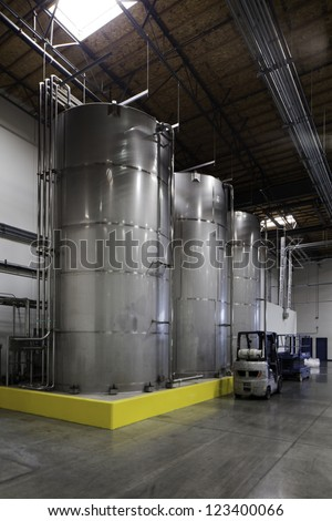 Huge silos and a forklift at bottling plant - stock photo