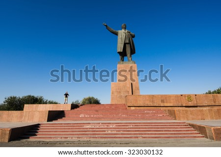Huge statue of Lenin with silhouette of standing woman, Osh, Kyrgyzstan - stock photo