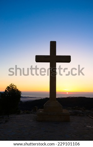 Huge stone cross against the background of a sunrise