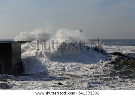 Huge wave rising through the new pier at the mouth of the Douro river, a good but dangerous fishing point, Porto, Portugal.