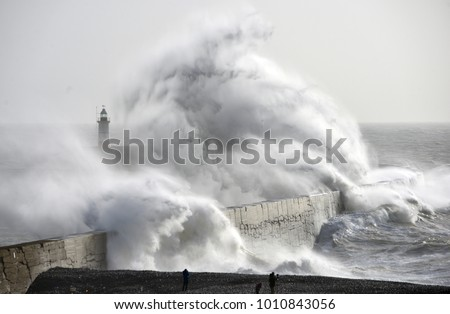 Huge waves crash against a sea wall and lighthouse during a winter storm, Newhaven, East Sussex