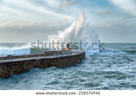 Huge waves crashing over the Monkey Hut on the stone pier at Portreath on the Cornwall coast - stock photo