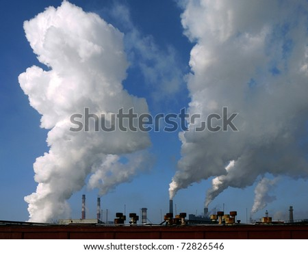 Huge white smoke from the pipes metallurgical plant, the blue sky