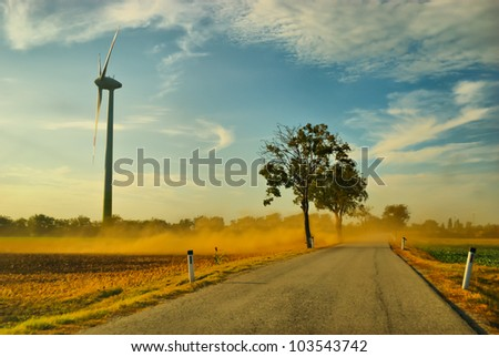 Huge wind turbine in the field throw up dust - stock photo