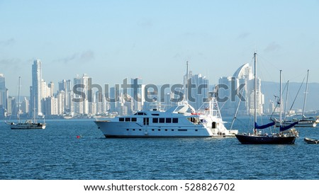 Huge yacht and Several boats anchored near Amador Causeway with the ever growing City of Panama in the background