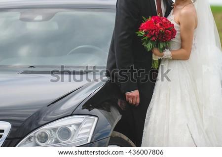 hugging bride and groom at black car - stock photo