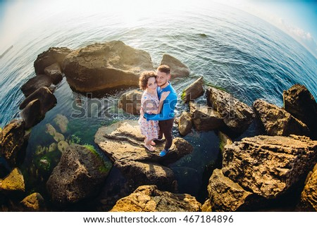 Hugging couple dressed in summer style stands on the yellow sea stones