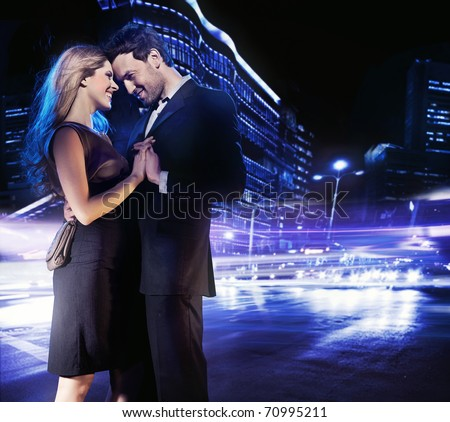 Hugging couple over city background - stock photo