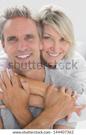 Hugging couple smiling at camera at home in bedroom - stock photo