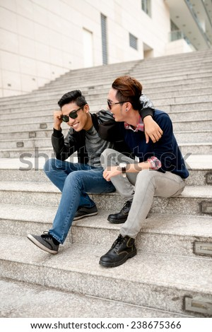 Hugging friends sitting on the steps and laughing - stock photo