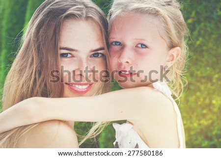 Hugging Happy Mother and Daughter Teenager on Green background. Toned - stock photo