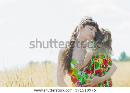 Hugging mother and her little daughter at summer meadow natural background outdoors - stock photo