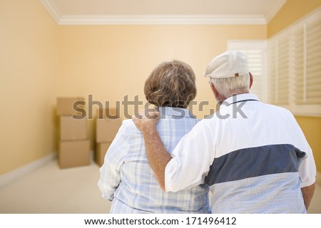 Hugging Senior Couple In Room Looking at Moving Boxes on the Floor. - stock photo